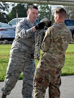 Tech. Sgt. Matthew Foster hands chains to Tech. Sgt. David Richards during a time chain drag competition at the 87th Aerial Port Squadron Port Dawg Challenge May 5, 2019. Both Airmen are load planning specialists with the 87th APS.