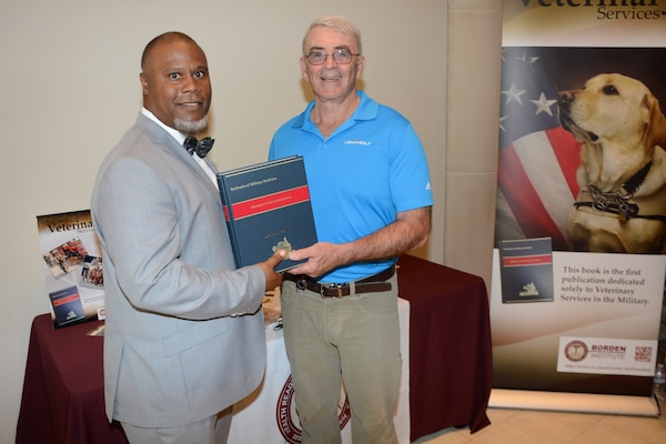 """Ernest J. Barner (left), Borden Institute public affairs, and Edward Lindeke (right), Borden Institute director, pose with a copy of the """"Military Veterinary Services"""" textbook."""