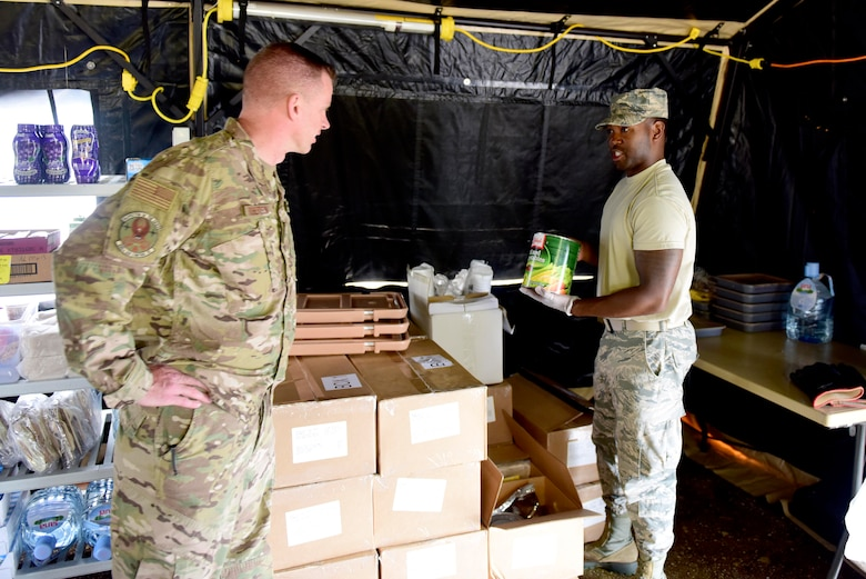 Airman 1st Class Jawan Dial, 31st Force Support Squadron assistant sports director, explains the contents of unitized group rations to Lt. Col. Brian Robertson, 606th Air Control Squadron commander, outside Pula, Croatia, May 28, 2019. The 31st FSS provided food services to the 606th ACS during exercise Astral Knight 19. (U.S. Air Force photo by Tech. Sgt. Tory Cusimano)