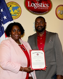 Huntley J. Bodden, right, director, Studies Analysis & Innovation Division, Quality Management Center (QMC), MARCORLOGCOM, receives the Commendation for Meritorious Civilian Service Medal from Carla Johnson, director, QMC, during a ceremony held in the Command Conference Room, Albany, GA., Jun 5.