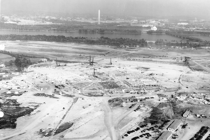 Construction begins on a massive plot of land. In the distance is the Washington Monument.