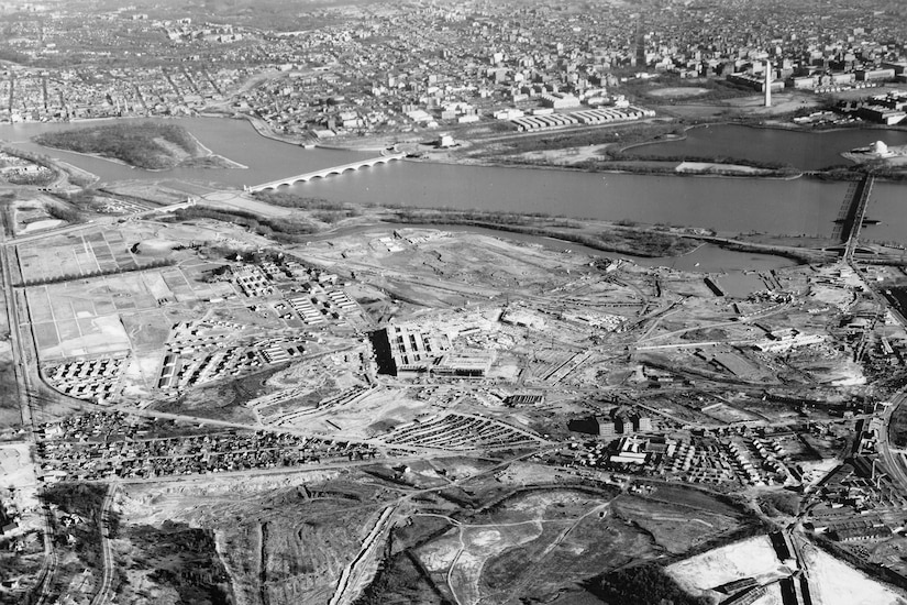 An aerial view of two sides of the Pentagon that are nearly complete during its construction. The Washington Monument and Potomac River are visible in the distance.