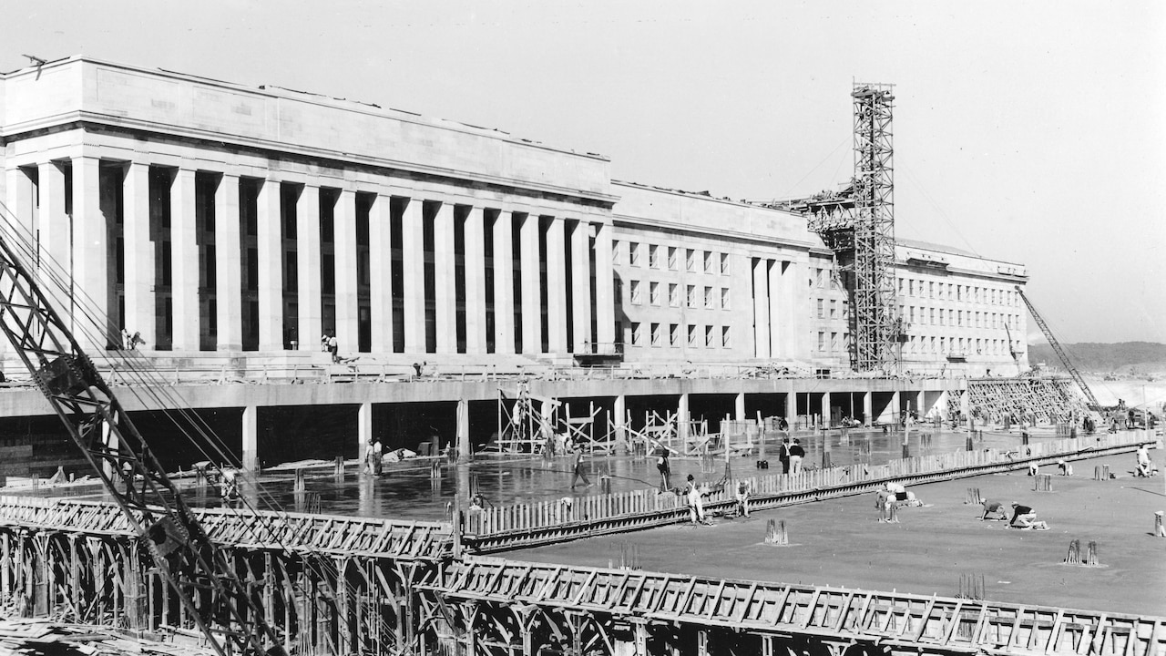 Scaffolding, a crane and construction crews surround a building that will eventually be the Pentagon.
