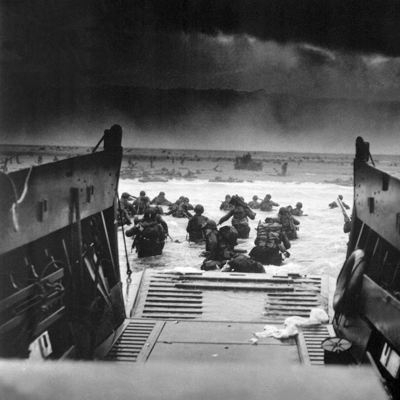 Landing on the coast of France under heavy Nazi machine gun fire are these American soldiers, shown just as they left the ramp of a Coast Guard landing boat, June 6, 1944.  CPhoM. Robert F. Sargent. (Coast Guard)