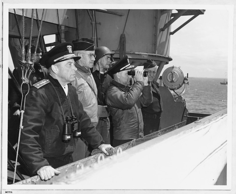 Senior U.S. officers watch operations from the bridge of USS Augusta (CA 31) off Normandy, June 8, 1944. They are from left to right: Commander Western Naval Task Force Rear Adm. Alan G. Kirk; Commanding General, U.S. First Army Lt. Gen. Omar N. Bradley; Chief of Staff Rear Adm. Arthur D. Struble; and Army Maj. Gen. Ralph Royce.