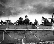 Troops and crewmen aboard a Coast Guard Landing Craft, Vehicle, Personnel (LCVP) approach Normandy beach on D-Day, June 6, 1944.