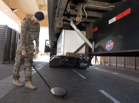 Senior Airman Jaden Cady, 56th Security Forces Squadron law enforcement controller, uses a mirror to inspect underneath a truck that is passing through the South Gate search pit, May 31, 2019, at Luke Air Force Base, Ariz.