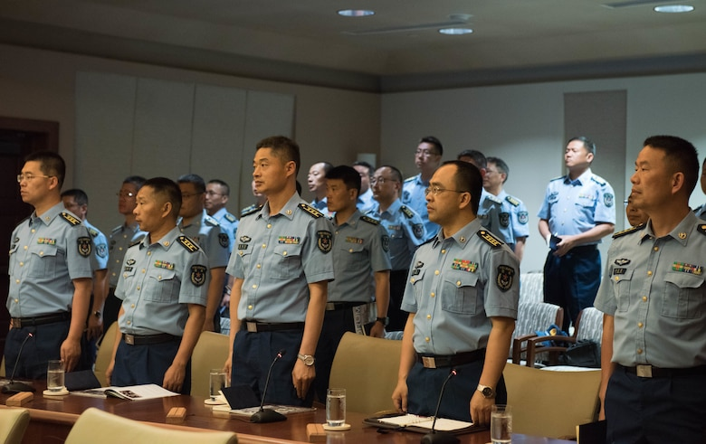 Members of the People's Liberation Army Air Force Command College wait for PLAAF and U.S. Air Force leadership to enter the room during a visit to Headquarters Pacific Air Forces at Joint Base Pearl Harbor-Hickam, Hawaii, May 28, 2019.