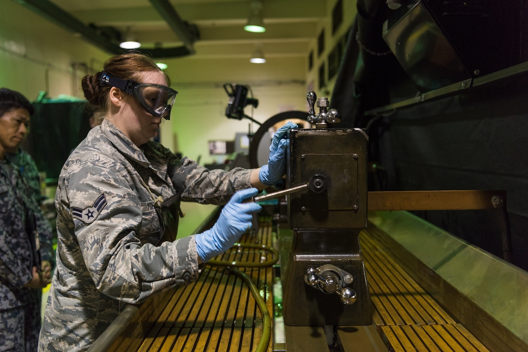 U.S. Air Force Airman 1st Class Jasmyn Yoder, nondestructive inspection apprentice assigned to the 18th Equipment Maintenance Squadron, demonstrates how to use the stationary magnetic particle inspection unit during a bilateral training exercise with the Japan Air Self-Defense Force May 23, 2019, on Kadena Air Base, Japan. This bilateral training exercise focused on teaching JASDF members the functions and purpose of aerospace ground equipment and nondestructive inspection flights. (U.S. Air Force photo by Airman 1st Class Cynthia Belío)