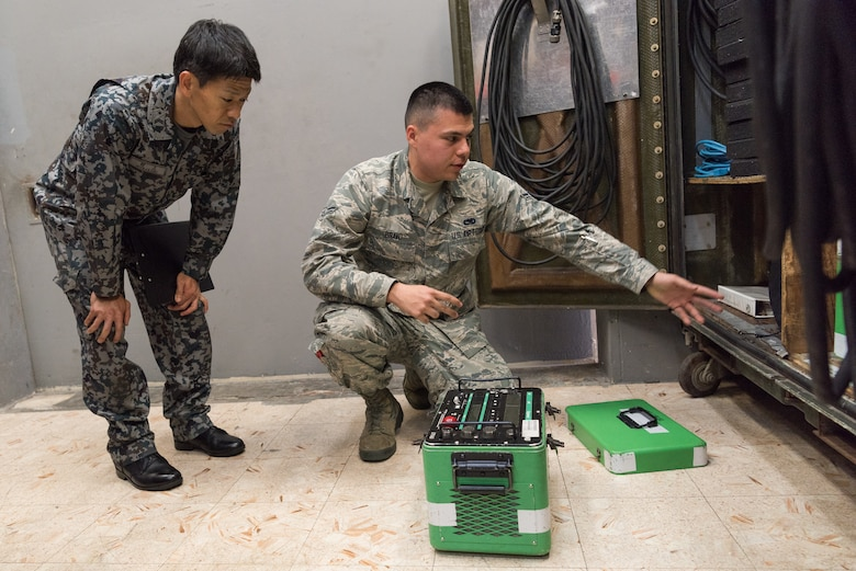 U.S. Air Force Airman 1st Class Miguel Bravo, nondestructive inspection journeyman assigned to the 18th Equipment Maintenance Squadron, demonstrates the use and function of the Lorad LPX-160 x-ray apparatus during a bilateral training exercise with the Japan Air Self-Defense Force May 23, 2019, on Kadena Air Base, Japan. This bilateral training exercise focused on teaching JASDF members the functions and purpose of aerospace ground equipment and nondestructive inspection flights. (U.S. Air Force photo by Airman 1st Class Cynthia Belío)