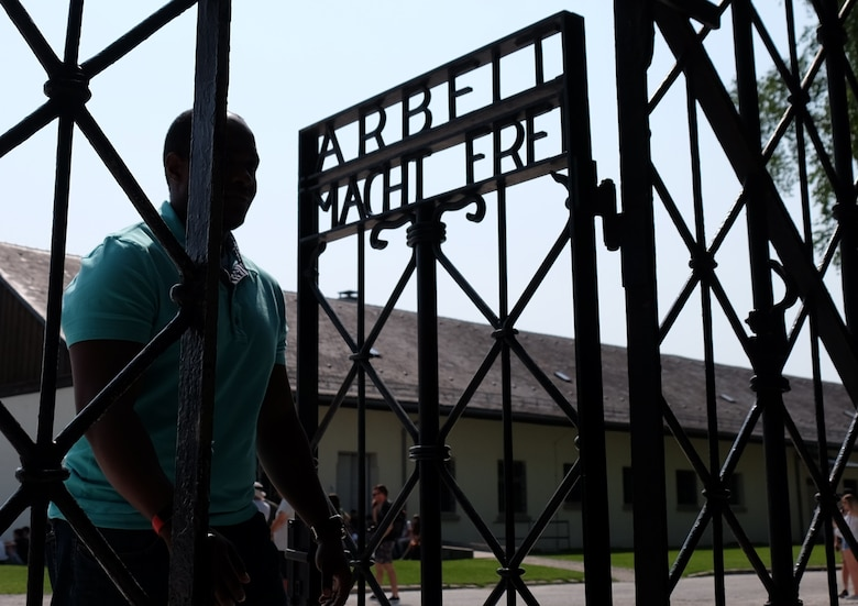 DACHAU, Germany—U.S. Army 2nd Lt. Adrian A. White, the S4 of the 83rd Combat Sustainment Support Battalion, 510th Regional Support Group, 7th Mission Command walks through the front gate of the Dachau Concentration Camp Memorial Site on the eve of the 75th anniversary of the World War II Allied D-Day invasion to end National Socialist Fascism in Europe on June 5, 2019. (U.S. Army photo by Sgt. Daniel J. Friedberg, 7th Mission Support Public Affairs)