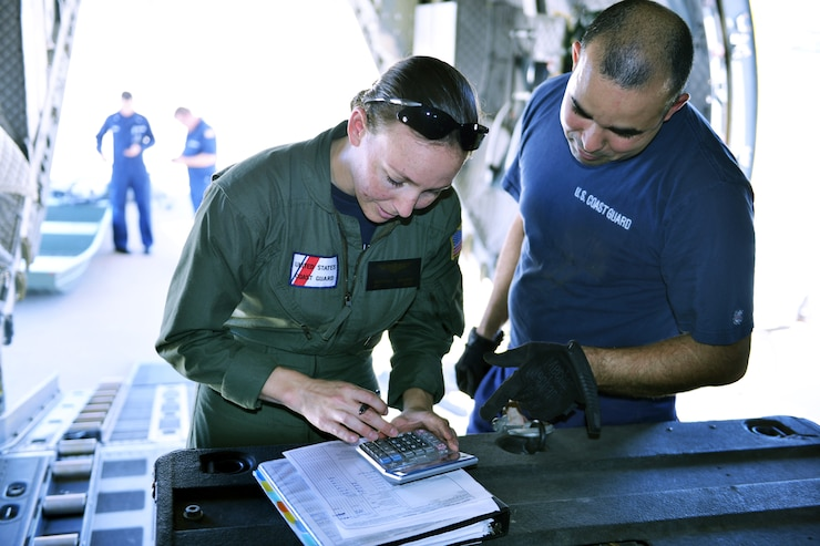 Petty Officer 3rd Class Brittany Willard, an aviation electronics technician from Coast Guard Air Station Sacramento, calculates the weight for approximately 3,000 pounds of gear loaded into the back of a C-27 Spartan aircraft at the air station, Aug. 28, 2017.