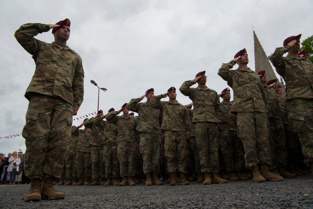 U.S. Army soldiers from the 82nd Airborne Division in Fort Bragg, North Carolina, 173rd Airborne Brigade Combat Team in Vicenza, Italy, and 93rd Infantry Brigade out of Oklahoma and Arkansas salute at the position of attention while the United States, German and French national anthems were played during a ceremony honoring all airborne troops and flight crew that served on D-Day in Picauville, France, June 4, 2019. The soldiers' presence in the ceremony highlights the strength of the U.S. commitment to European security as they pay respects during the D-Day 75th anniversary commemorations. (U.S. Air Force photo by Senior Airman Kristof J. Rixmann)