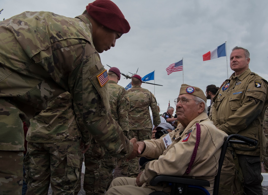 """A U.S. Army airborne infantryman shakes the hand of retired Private First Class Joseph Morettini, 82nd Airborne, 508th Regiment, Easy Company, during a ceremony held to honor all airborne troops and flight crew that served on D-Day in Picauville, France, June 4, 2019. On June 6, 1944, Morettini dropped from midnight skies into Normandy with the objective to overtake an enemy stronghold near Picauville. During the ceremony's conclusion, Morettini remarked to each active U.S. airborne infantrymen he shook hands with: """"I dropped here 75 years ago."""" (U.S. Air Force photo by Senior Airman Kristof J. Rixmann)"""