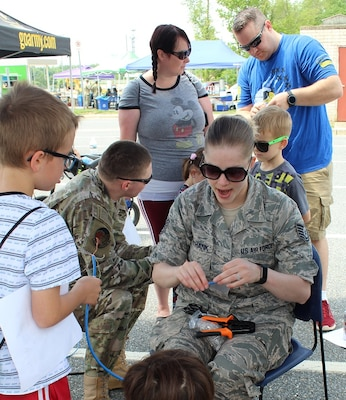 Air Force Technical Sgt. Jennifer Unthank demonstrates basic cable making to a young visitor at the Armed Forces & National Police Celebration. The kids provided the last touch to the cables by crimping the ends.