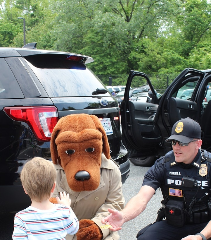McGruff and Officer Perkins, NSA Police, greet a young visitor at the Armed Forces & National Police Celebration.