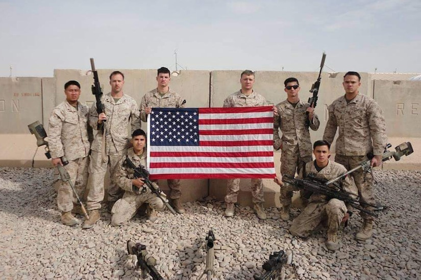 Eight Marines pose with an American flag in front of a cement barricade in Afghanistan.