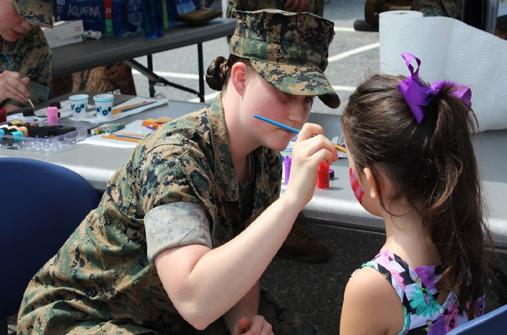 A Marine from the Marine Cryptologic Support Battalion paints one of many faces at the Armed Forces & National Police Celebration. The Marines also allowed visitors to dress in combat gear.