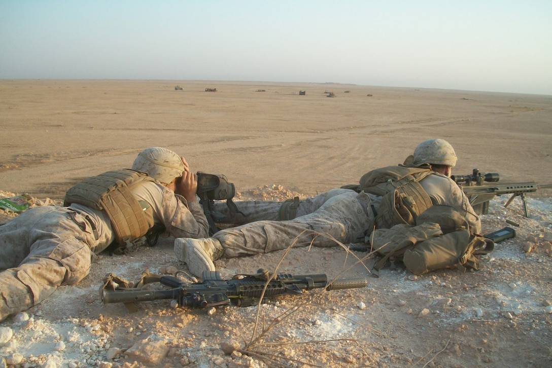 Two Marines in the prone position engage simulated targets.
