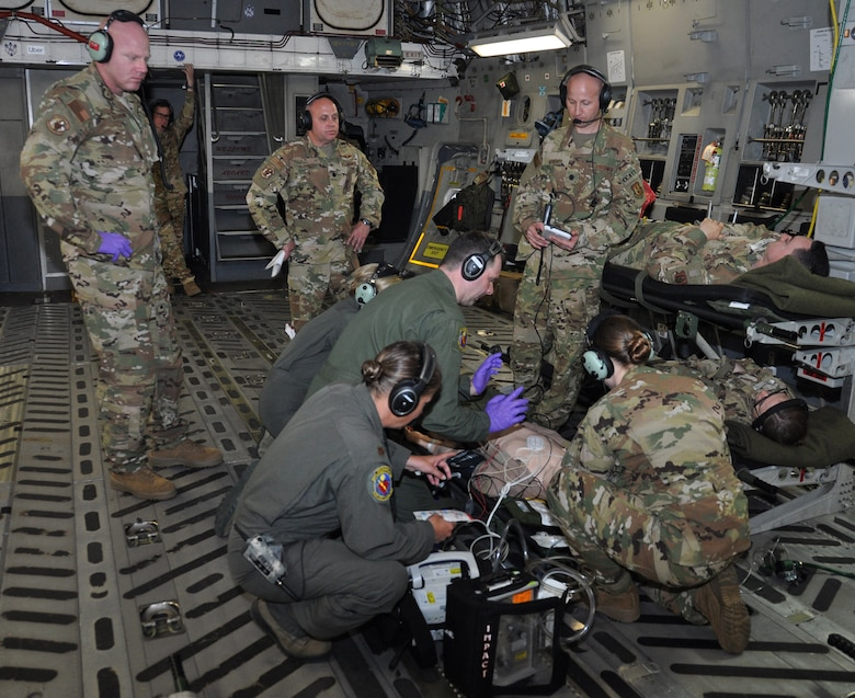 Lt. Col. Derek Sorensen, (standing far right) U.S. Air Force School of Aerospace Medicine medical director for en route care training, evaluates a 445th Aeromedical Evacuation Squadron crew during an AE readiness flight, May 8, 2019.