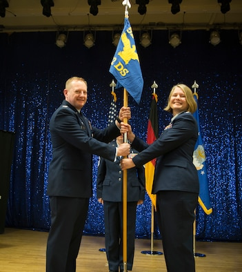 U.S. Air Force Col. Edward Lagrou, 52nd Medical Group commander, left, gives the ceremonial guidon to U.S. Air Force Lt. Col. Elizabeth Bowman, incoming 52nd Dental Squadron commander, right, during the 52nd DS change of command ceremony at Spangdahlem Air Base, Germany, June 6, 2019.