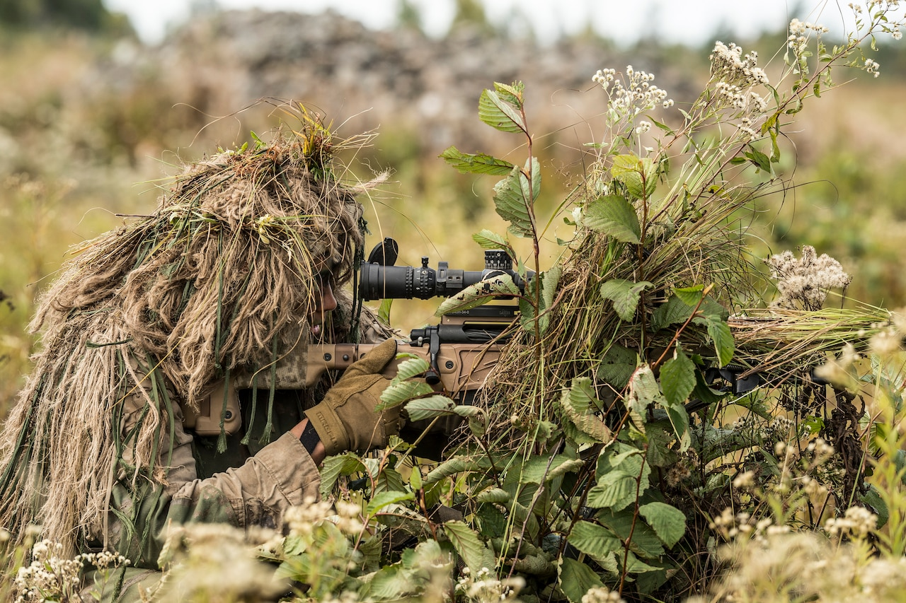 A Marine, camouflaged by a ghillie suit  looks through the sight of his sniper rifle.