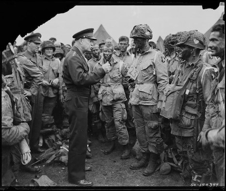 "General Dwight D. Eisenhower gives the order of the Day on June 6, 1944.  ""Full victory-nothing else"" to paratroopers in England, just before they board their airplanes to participate in the first assault in the invasion of the continent of Europe.