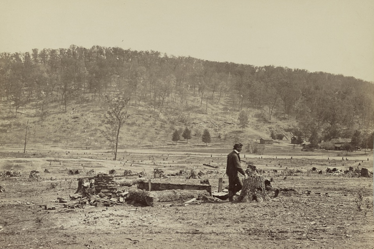 A man walks in a field in front of a ridge covered in trees.