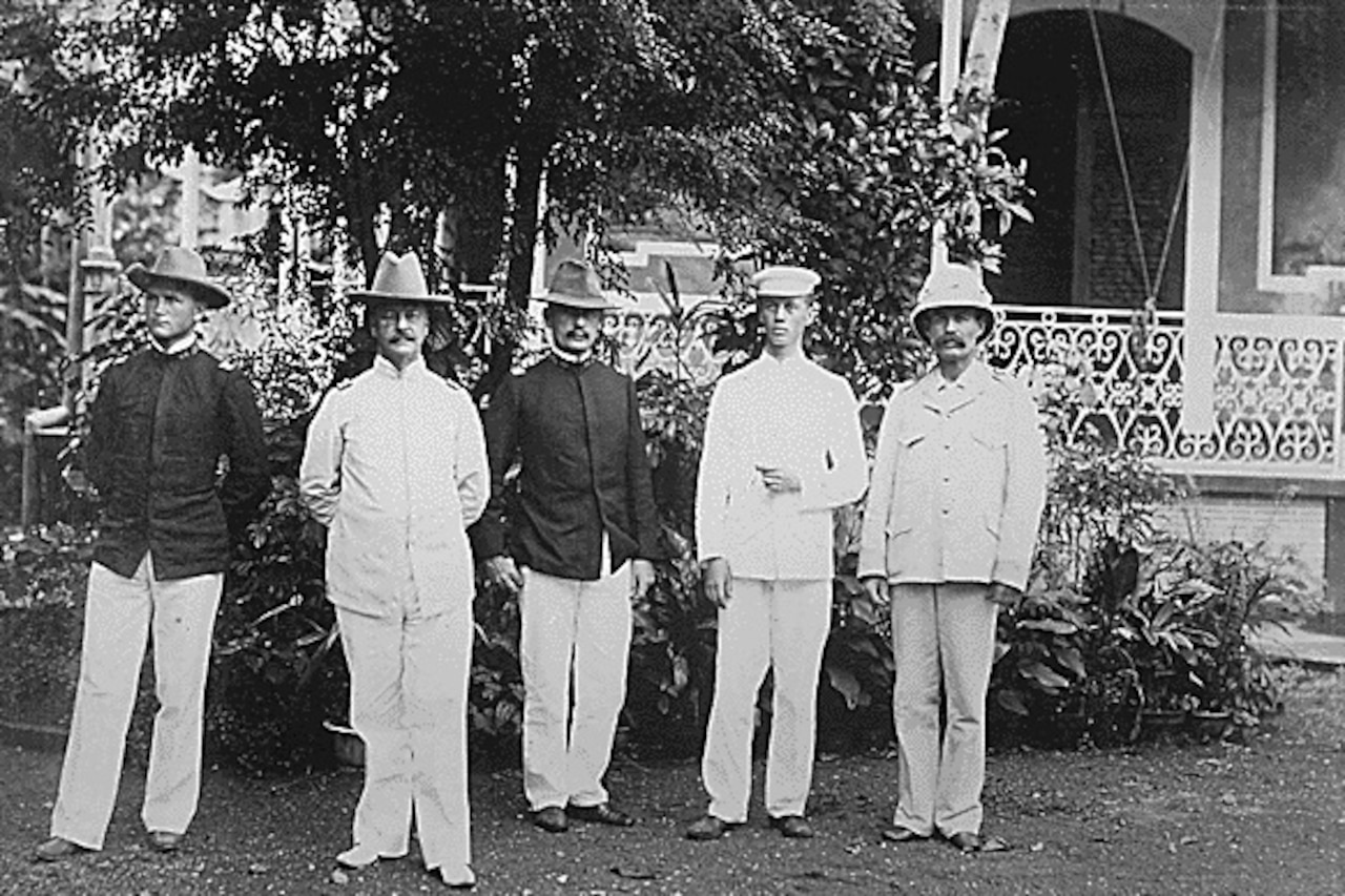 Five men pose for a photo in front of a building, trees and a shrub.