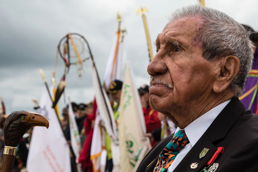 A vet looks out at a ceremony, amid a crowd holding flags and Native American ceremonial items.