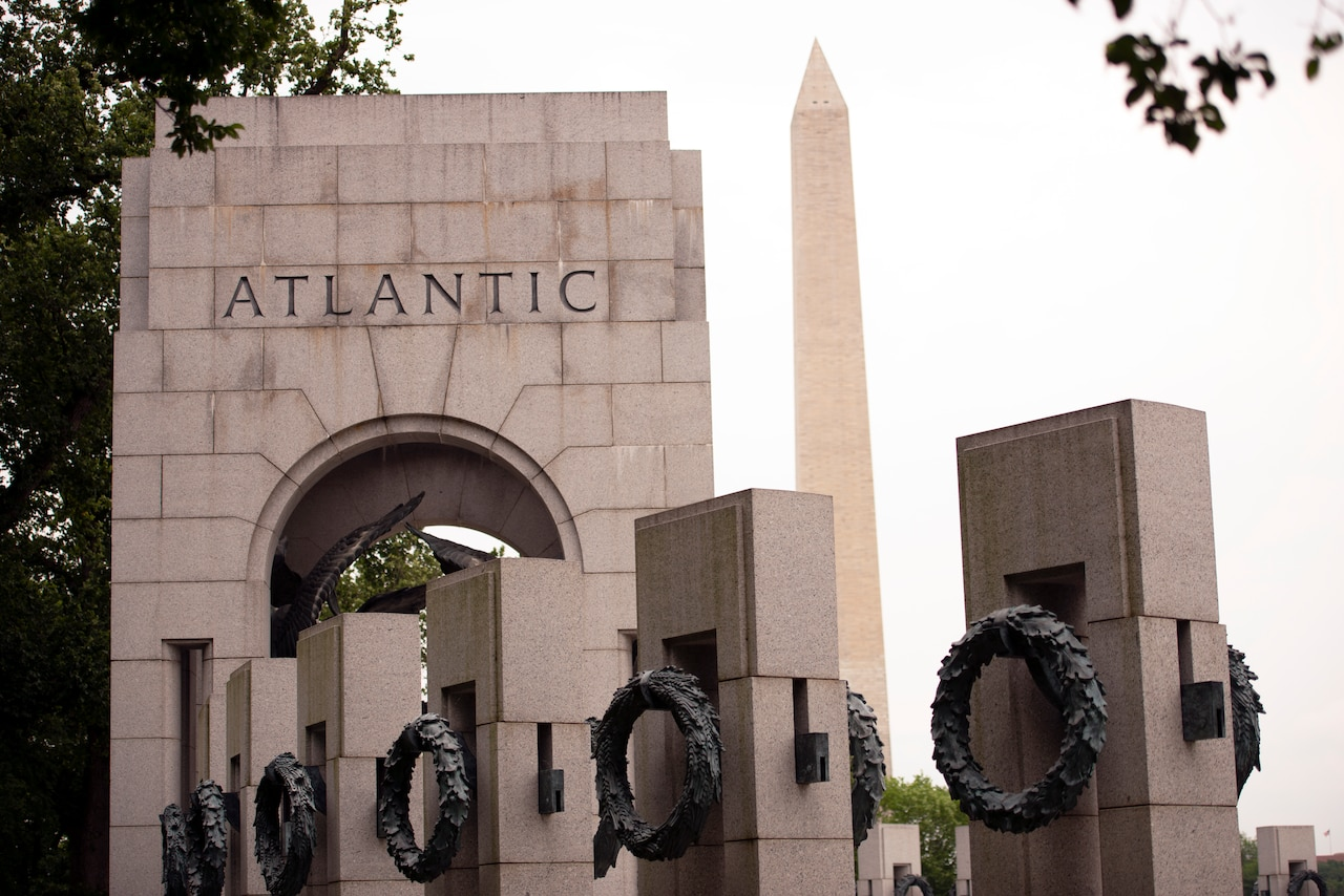 "A stone arch bears the word ""Atlantic."" In the background looms the Washington Monument.  In the foreground are individual pillars with bronze wreaths."