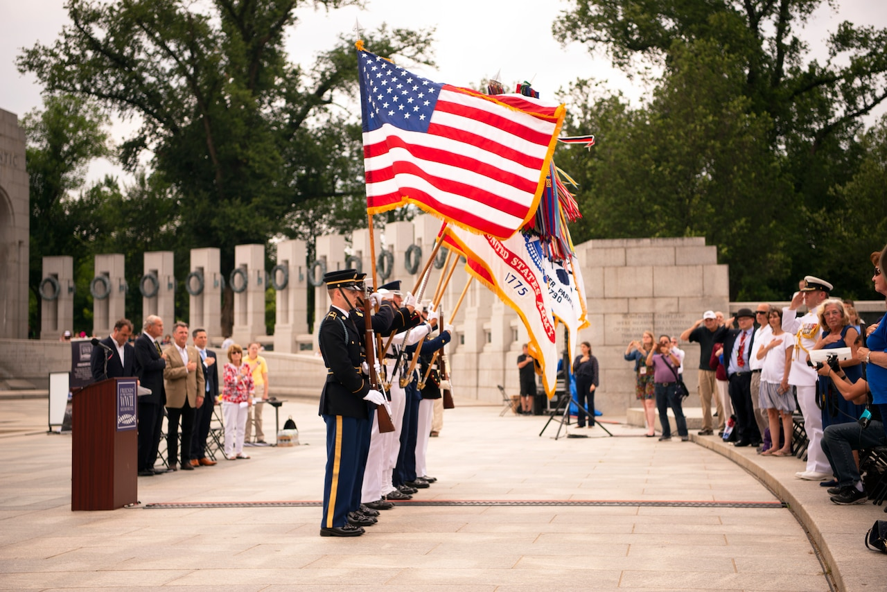Service members stand in a line, each holding a flag.