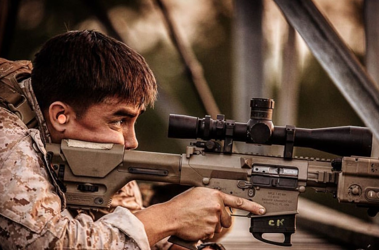 A Marine looks through the scope of an M110 semi-automatic sniper rifle.