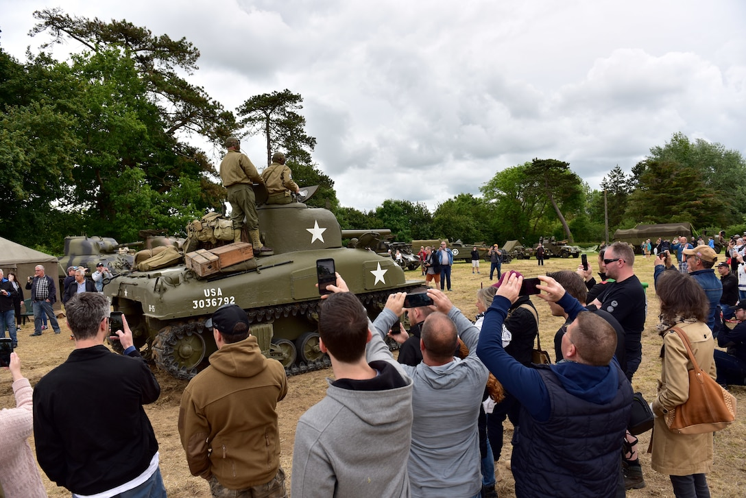 A tank drives by a crowd