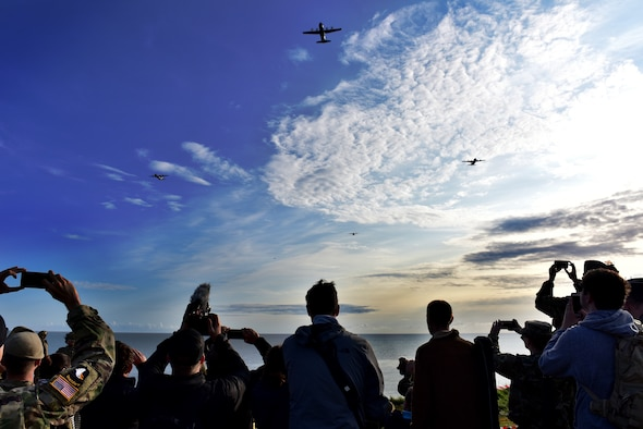 A C-130J flies over a crowd