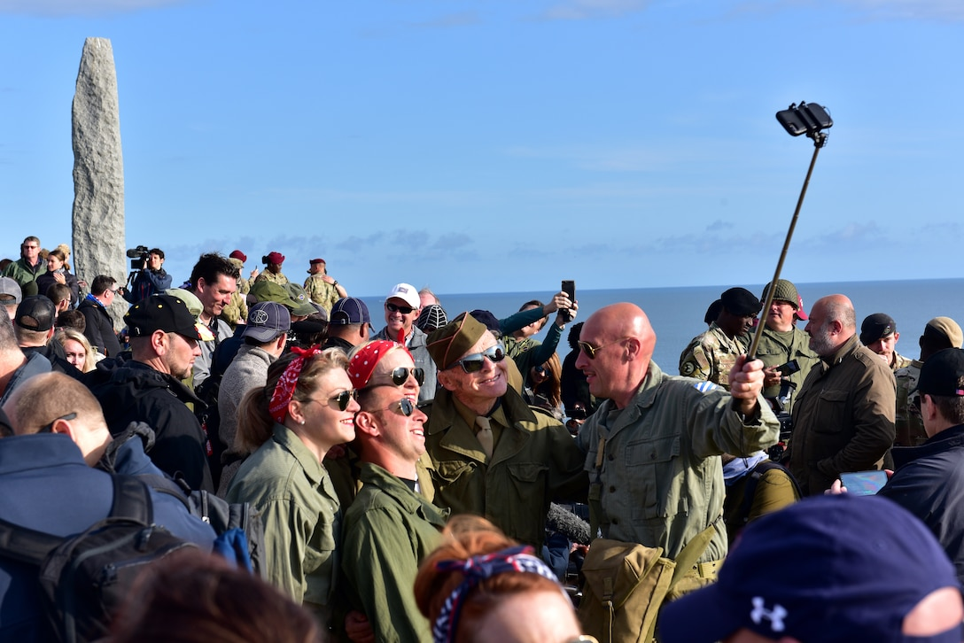A C-130J flies over a crowd