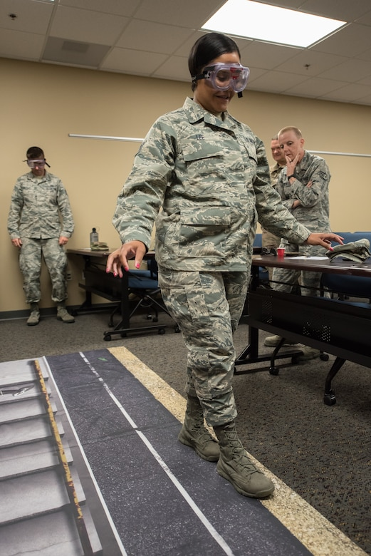 Staff Sgt. Erin Lee, a command support specialist in the Kentucky Air National Guard's 123rd Airlift Wing, participates in a wellness class while wearing goggles to mimic the effects of alcohol impairment May 19, 2019, in Savannah, Ga. The class was part of Maintenance University, a four-day event held at the Combat Readiness Training Center from May 19 to 22.