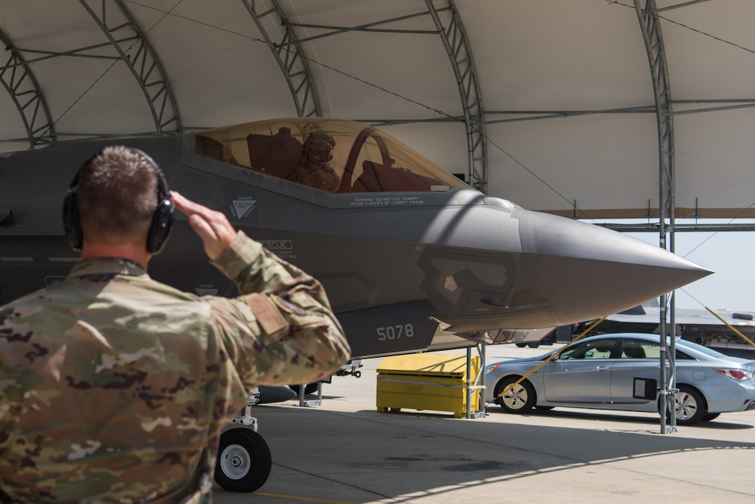 "An F-35 Lightning II Demonstration Team maintainer salutes U.S. Air Force Capt. Andrew ""Dojo"" Olson, F-35 Lightning II Demonstration Team pilot, before takeoff at Joint Base Langley-Eustis, Virginia, June 6, 2019."