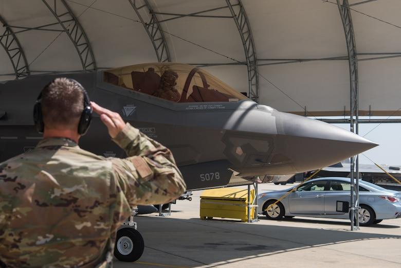 "An F-35 Lightning II Demonstration Team maintainer salutes U.S. Air Force Capt. Andrew ""Dojo"" Olson, F-35 Lightning II Demonstration Team pilot, before takeoff at Joint Base Langley-Eustis, Virginia, June 6, 2019."