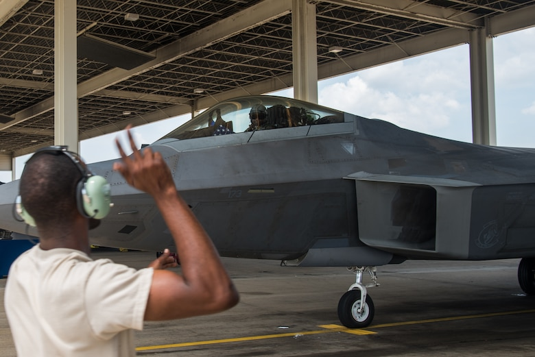 """An F-22 Maintainer marshals U.S. Air Force Maj. Paul """"Loco"""" Lopez, F-22 Raptor Demonstration Team pilot, before takeoff at Joint Base Langley-Eustis, Virginia, June 6, 2019."""