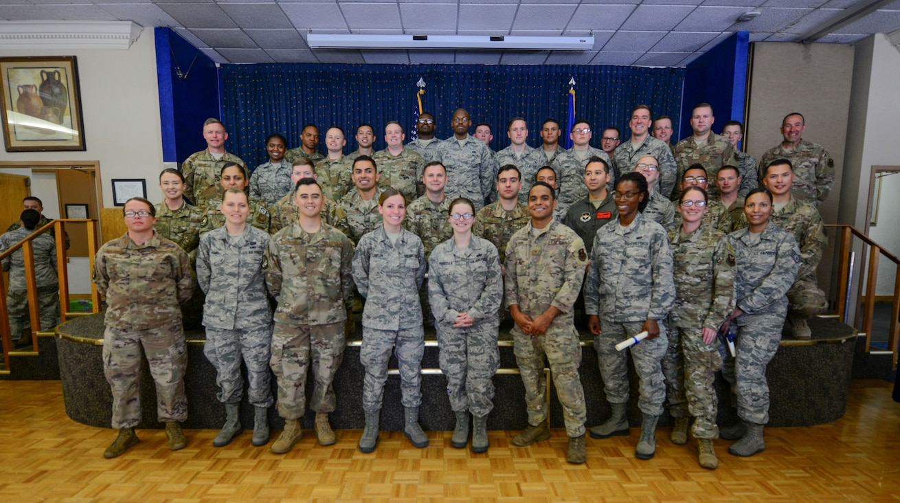 Community College of the Air Force (CCAF) graduates pose for a group photo after their graduation ceremony held at the Mountain View Club on June 5, 2019. Airmen must successfully complete technical training as well as additional classes outside of work in order to receive a CCAF degree. (U.S Air Force photo by Senior Airman Alexandria Crawford)