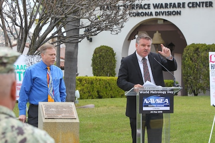 Naval Surface Warfare Center, Corona Division (NSWC Corona) Measurement Science and Engineering Department Head Richard Schumacher, right, and Measurement Science and Engineering Department Chief Engineer Robert Fritzsche, left, speak to members of the command during the World Metrology Day celebration.
