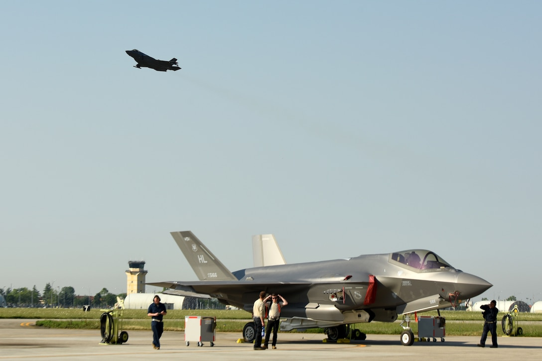 An F-35A Lightning II fighter jet sits on the flightline while another F-35A takes off during Astral Knight 2019 June 3, 2019, at Aviano Air Base, Italy. The F-35A contains state-of-the-art tactical data links that provide secure sharing of data among its flight members as well as other airborne, surface and ground-based platforms. The Airmen are deployed from the active duty 388th and Reserve 419th Fighter Wings at Hill Air Force Base, Utah. (U.S. Air Force photo by Tech. Sgt. Jim Araos)
