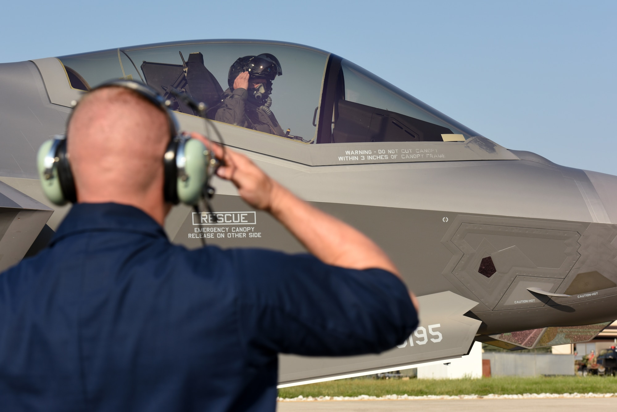 Senior Airman Christopher Kuhn, 421st Aircraft Maintenance Unit crew chief, salutes Lt. Col. Max Cover, 421st Fighter Squadron F-35A Lightning II fighter pilot, during Astral Knight 2019 on June 3, 2019, at Aviano Air Base, Italy. The F-35s are participating in Astral Knight 2019, a multinational integrated air and missile defense exercise that enhances relationships with allies and improves overall coordination with partner militaries during times of crisis. The Airmen are deployed from the active duty 388th and Reserve 419th Fighter Wings at Hill Air Force Base, Utah. (U.S. Air Force photo by Tech. Sgt. Jim Araos)
