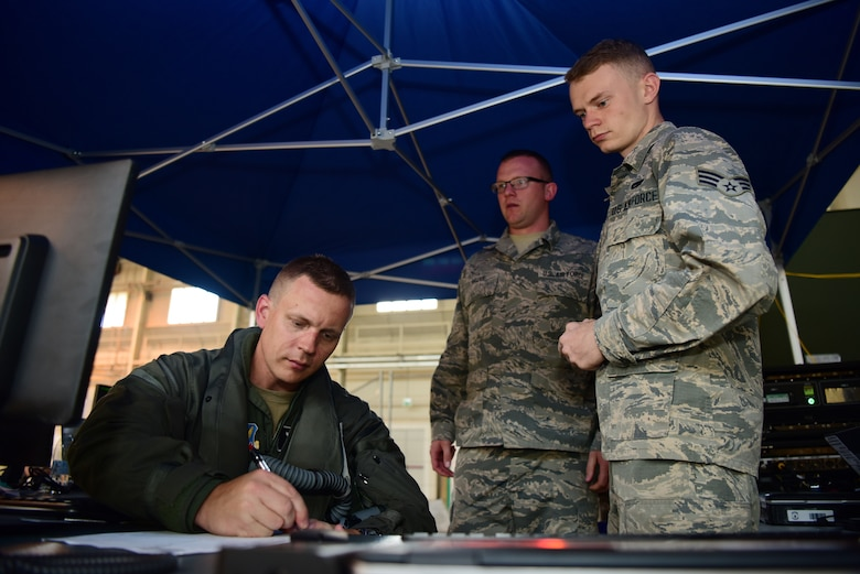 Senior Airmen Julian Cornwell and Justin Sauve, 388th Aircraft Maintenance Squadron debrief technicians, collects flight information from Lt. Col. Max Cover, 421st Fighter Squadron F-35A fighter pilot, during Astral Knight 2019 on June 3, 2019, at Aviano Air Base, Italy. The collected information was uploaded into the Autonomic Logistics Information System to maintain the F-35A's mission readiness. The Airmen are deployed from the active duty 388th and Reserve 419th Fighter Wings at Hill Air Force Base, Utah. (U.S. Air Force photo by Tech. Sgt. Jim Araos)
