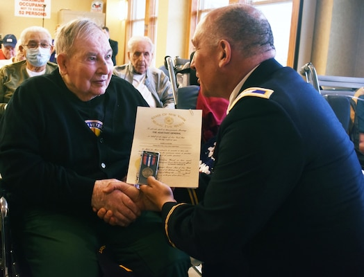 New York Army National Guard Col. Richard Goldenberg presents former Army  Pfc. and World War Ii veteran  Harry Myers with a New York State Medal of Merit at the 75th Anniversary of D-Day commemorative celebration at the Veterans' Home in Oxford, N.Y., on June 6th, 2019.