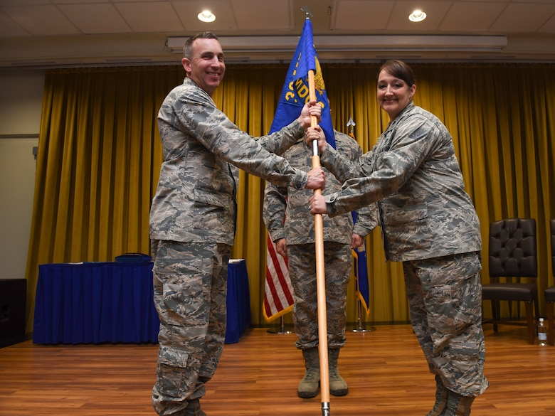 Col. Christopher Estridge, 39th Medical Group commander, left, passes the guidon to Lt. Col. Dana Adrian, 39th Medical Operations Squadron incoming commander, during the change of command ceremony June 7, 2019, at Incirlik Air Base, Turkey. The change of command is a military tradition held to allow all of the units to witness the formal change of authority. (U.S. Air Force photo by Staff Sgt. Matthew J. Wisher)