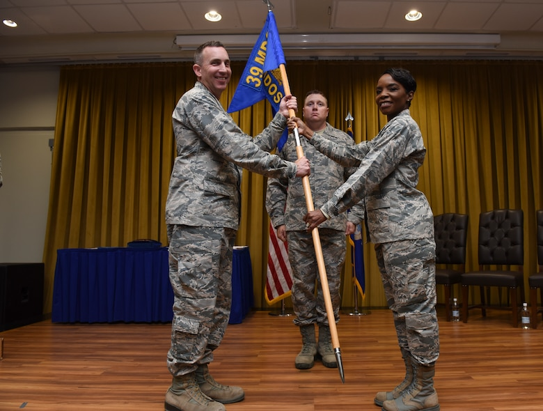 Lt. Col. Sarah Evans, 39th Medical Operations Squadron outgoing commander, right, passes the guidon to Col. Christopher Estridge, 39th Medical Group commander, during the change of command ceremony June 7, 2019, at Incirlik Air Base, Turkey. The passing of the guidon symbolizes one commander relinquishing command and all of the responsibilities to the incoming commander. (U.S. Air Force photo by Staff Sgt. Matthew J. Wisher)