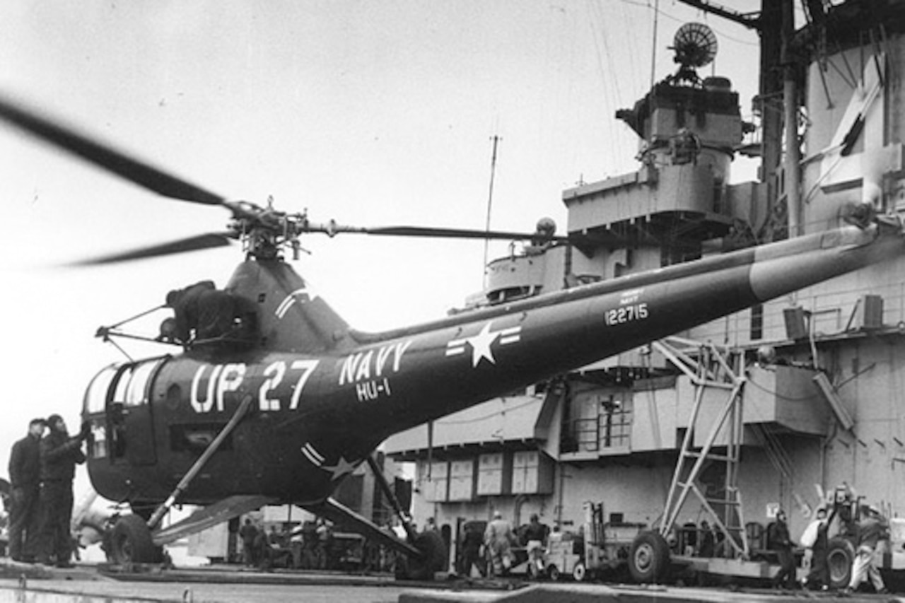 A black and white photograph of a military helicopter on board a ship.