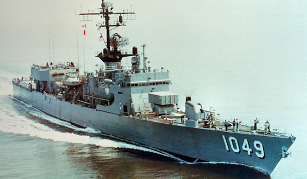 A military ship  moves through the water.